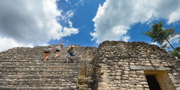 Tourists climb the stairs of Caana pyramid in Caracol
